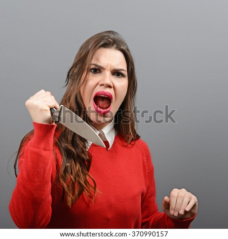 Portrait of killer woman with knife against gray background - stock photo