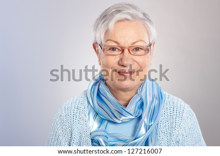 Portrait of kind elderly lady in light blue, smiling, looking at camera. - stock photo