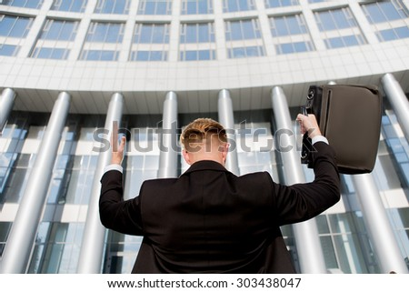Portrait of king of the world with his hands raised. Young successful businessman in front of the office building with brief case. - stock photo