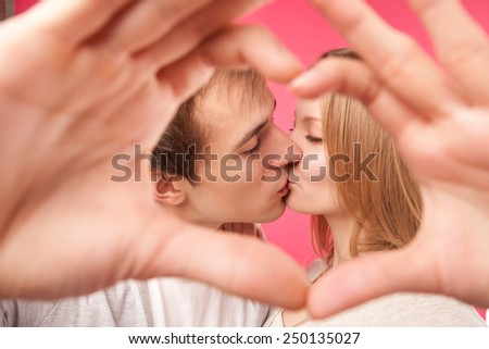 Portrait of kissing beauty girl and her handsome boyfriend making shape of heart by their hands and shown through it. Happy joyful family. Love concept. Heart sign. Laughing happy lovers.  - stock photo