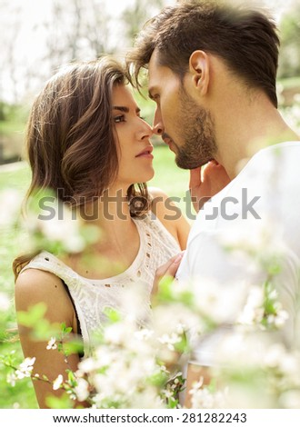Portrait of kissing couple in the blooming garden - stock photo