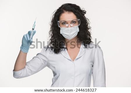 Portrait of lady surgeon in glasses showing syringe isolated on white background - stock photo
