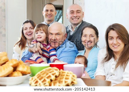 Portrait of  large joyful three generations family sits on sofa in livingroom  - stock photo