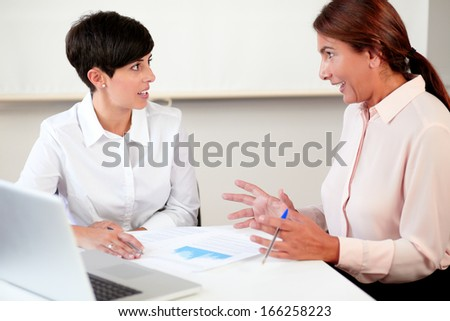Portrait of latin professional women working on documents while sitting in the office - stock photo