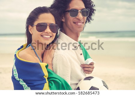 Portrait of latino couple with Brasil flag and soccer ball - stock photo
