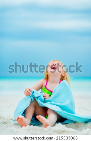 Portrait of laughing baby girl in towel sitting on beach - stock photo