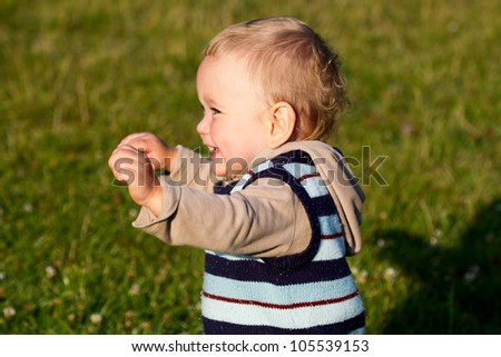 Portrait of laughing baby on nature background - stock photo