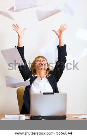 Portrait of laughing businesswoman throwing up sheets of paper with sitting at the table with the opened laptop and a white cup on it - stock photo