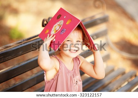 Portrait of laughing little girl with a book on his head outdoors - stock photo