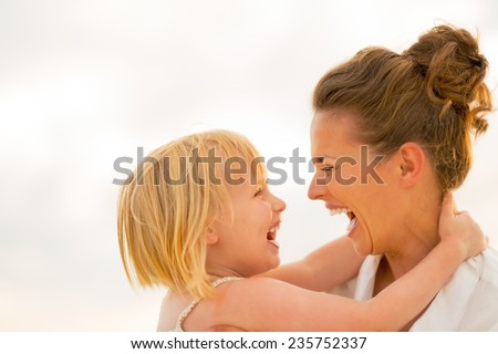 Portrait of laughing mother and baby girl hugging on beach at the evening - stock photo