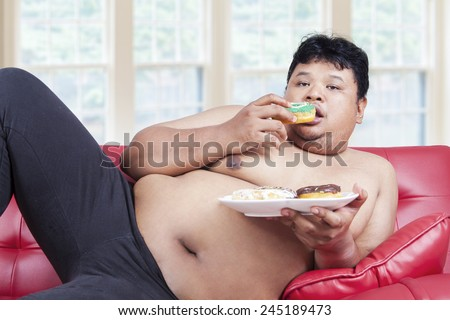 Portrait of lazy overweight person eating donuts while sitting on the sofa at home - stock photo