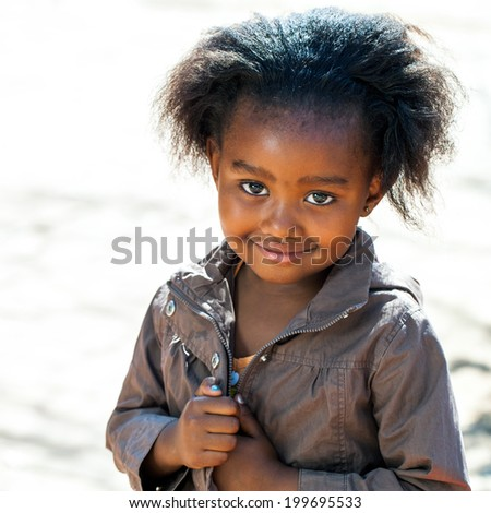 Portrait of Little African girl in brown jacket outdoors. - stock photo