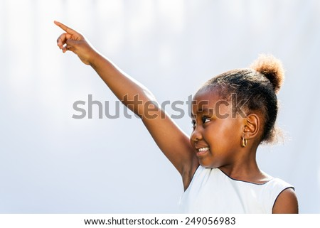 Portrait of little African girl pointing with finger and looking at corner.Isolated against light background. - stock photo