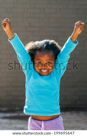 Portrait of little African girl raising arms outdoors. - stock photo