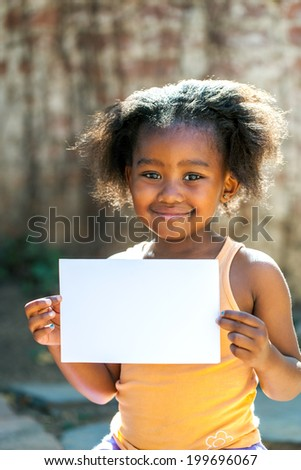 Portrait of little African girl showing blank white card outdoors. - stock photo
