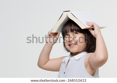 Portrait of little Asian child thinking and put a book on top with copy space - stock photo
