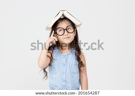 Portrait of little Asian child thinking with a book on top - stock photo