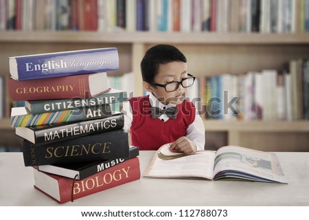Portrait of little asian elementary school student studying by reading books of lessons. shot in the library - stock photo