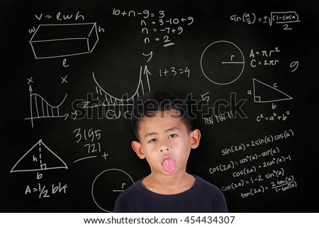 Portrait of little Asian student boy with his tongue out getting sick and bored of math lesson, over blackboard with mathematics schemes doodle drawn on it - stock photo