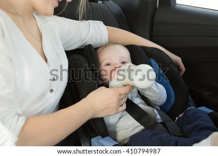 Portrait of little baby boy drinking milk from bottle on car back seat - stock photo