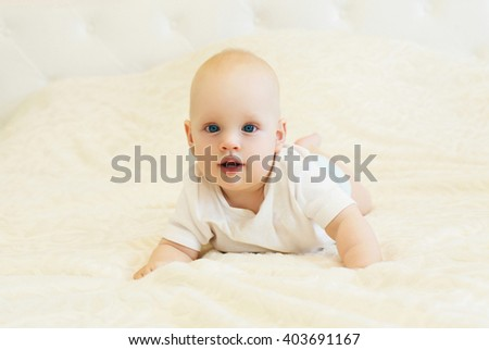 Portrait of little baby crawls on the bed at home - stock photo