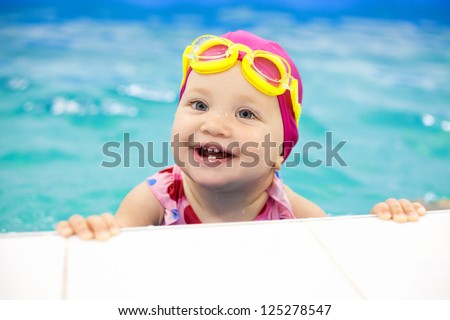 Portrait of little baby swimming  in swimming pool - stock photo