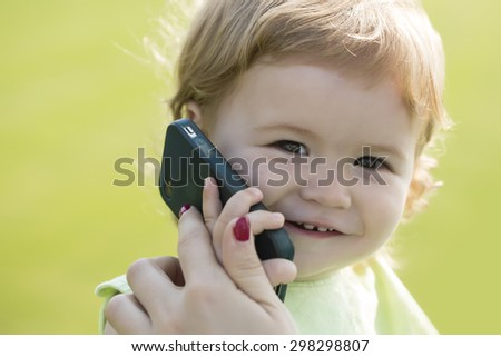 Portrait of little beautiful smiling baby boy with blonde curly hair and cute face holding and speaking on black mobile phone sunny day outdoor on green grass background, horizontal picture - stock photo