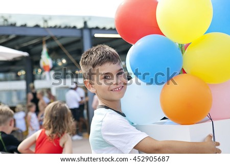 Portrait of little blond boy with colorful balloons; outside birthday party; happy birthday boy - stock photo