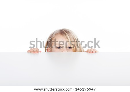 Portrait of little blond girl peeking over table isolated over white background - stock photo