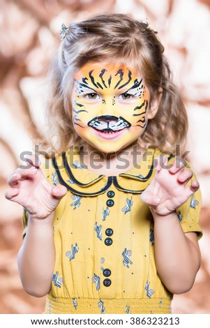 Portrait of little blond girl with painted face - stock photo