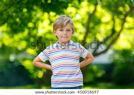 Portrait of little blonde preschool kid boy in summer. Child with green backgrounds on warm summer day. Happy carefree childhood. - stock photo