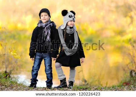 portrait of little boy and girl outdoors in autumn - stock photo