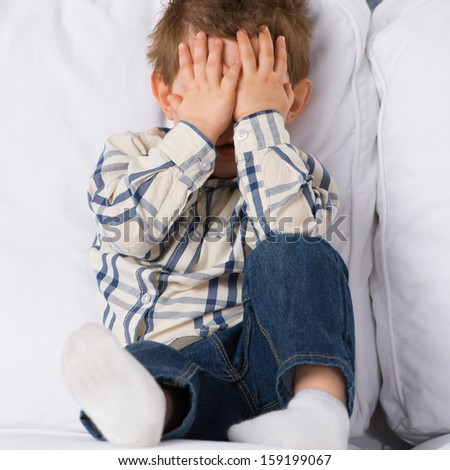 Portrait of little boy closing eyes with his hands at home - stock photo