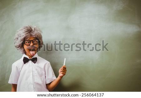 Portrait of little boy dressed as senior teacher in front of blackboard - stock photo