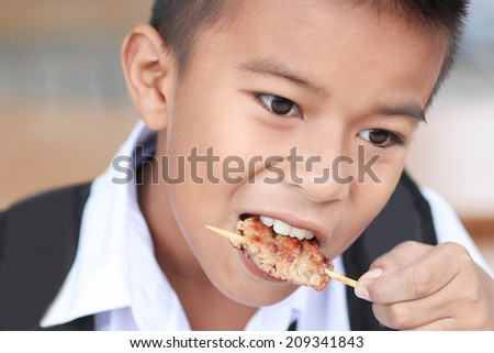 Portrait of little boy eating grilled pork. - stock photo