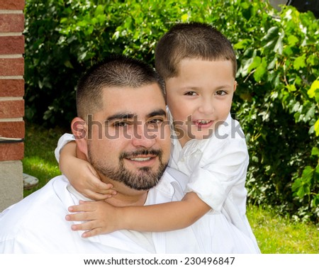 portrait of little boy hugging his father - stock photo