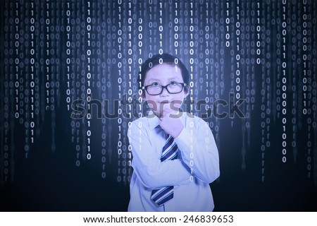 Portrait of little boy in front of a computer screen with binary code on it - stock photo