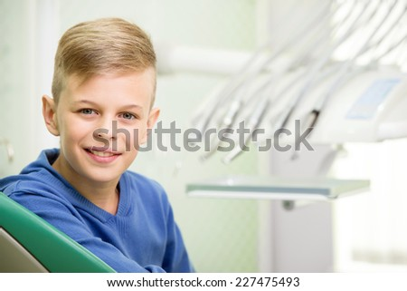 Portrait of little boy in the dentist's office. He is looking at camera. - stock photo