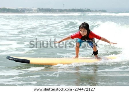 portrait of little boy learn to surf at ocean - stock photo