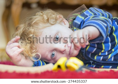 Portrait of  little boy playing with toy on the floor - stock photo