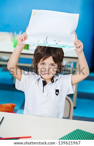 Portrait of little boy showing drawing paper in classroom - stock photo