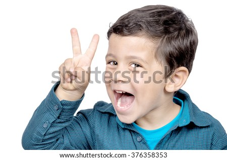 Portrait of little boy showing victory hand sign on white background - stock photo