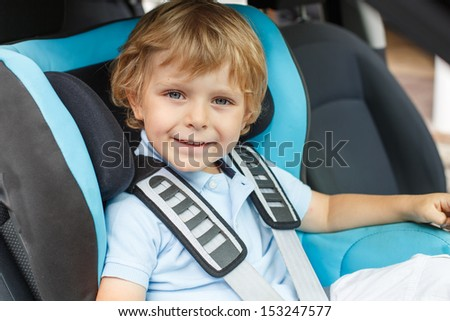 Portrait of little boy sitting in safety car seat - stock photo