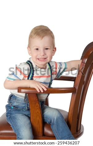 Portrait of little boy sitting sideways in an armchair leaning on the arm isolated on white background - stock photo
