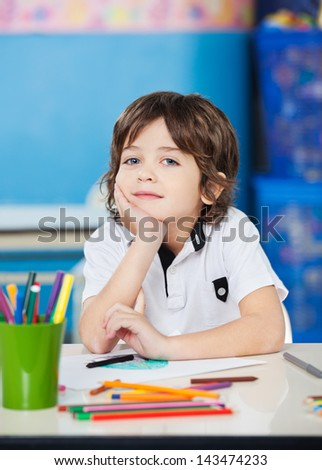 Portrait of little boy sitting with hand on chin in drawing class - stock photo