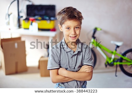 Portrait of little boy standing with arms crossed - stock photo