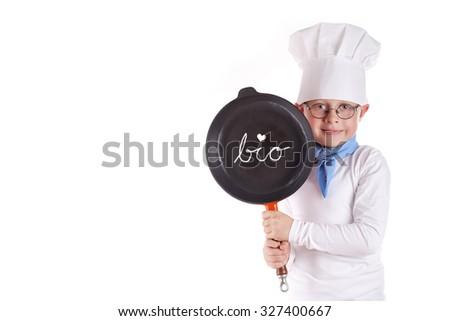 Portrait of little boy wearing chef uniform, little boy cook holding pan - stock photo