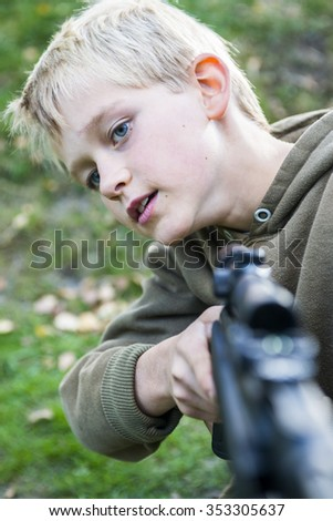 Portrait of little boy with airgun shooting outdoors, air rifle with telescopic sights - stock photo