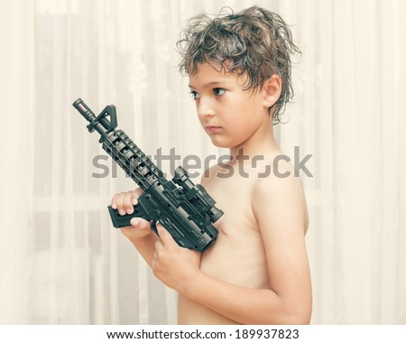 Portrait of little boy with automatic weapon on white background indoors - stock photo