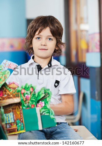 Portrait of little boy with popup book sitting on desk in classroom - stock photo